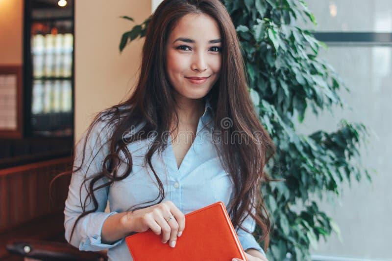 Portret van mooi charmant donkerbruin lang haar die Aziatisch meisje met oranje leeragenda glimlachen dichtbij het venster bij ko stock afbeeldingen