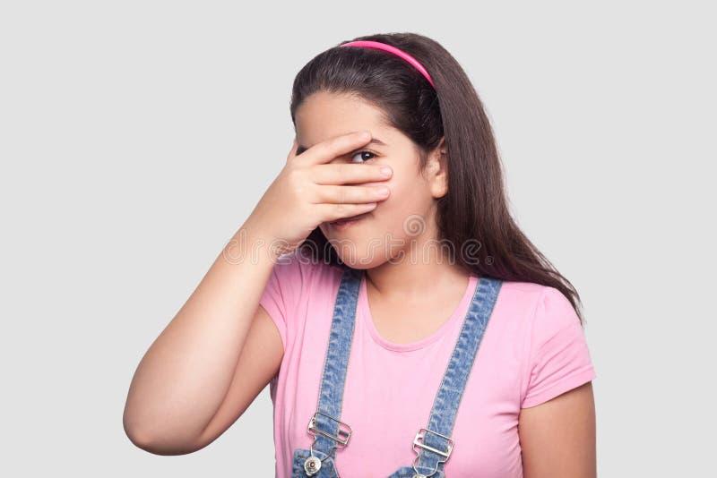 Portret van mooi donkerbruin jong meisje in toevallige stijl, roze t-shirt en blauwe denimoverall die en zich camera bevinden bek stock foto's