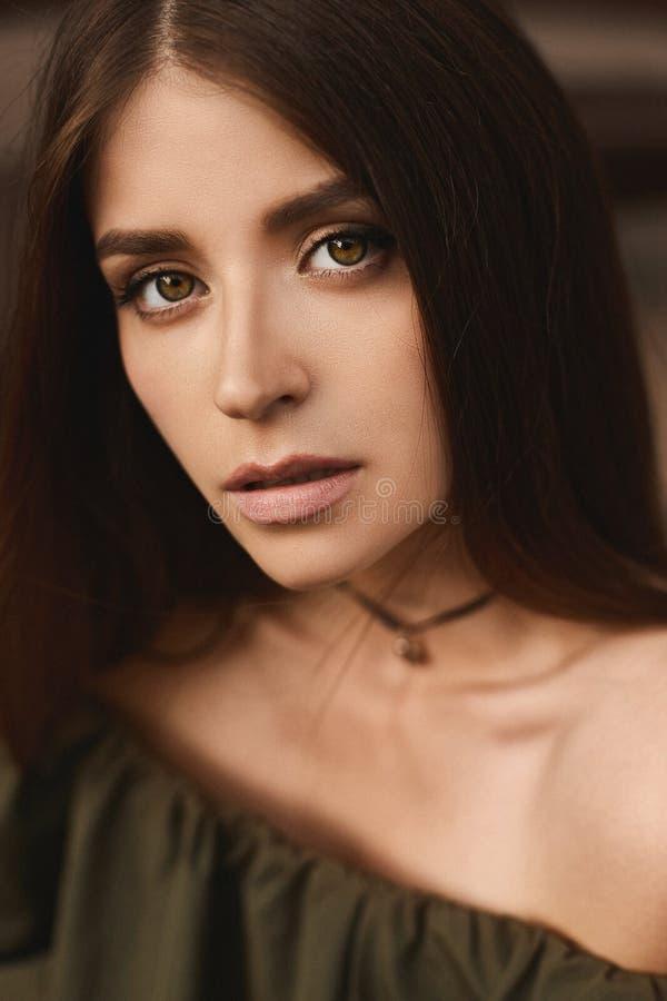 Portret van mooi donkerbruin modelmeisje met donkergroene ogen en met zachte make-up in modieuze donkergroene kleding stock foto