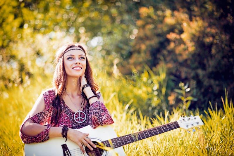 Portret van mooi glimlachend hippiemeisje met gitaar Mistig dalingseiland stock fotografie