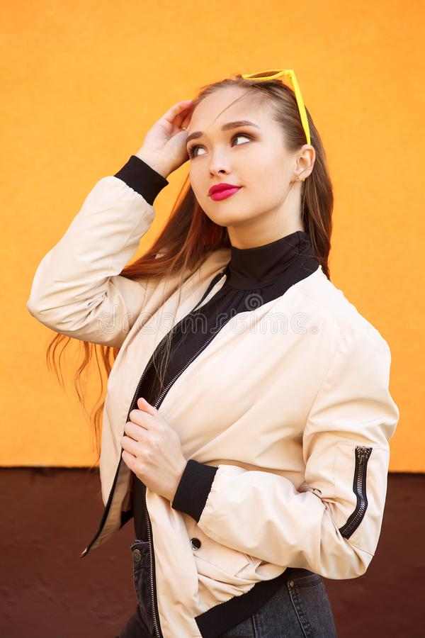 Portret van mooi hipstermeisje in zonnebril op oranje achtergrond Perfecte de zomersamenstelling en stijl stock fotografie