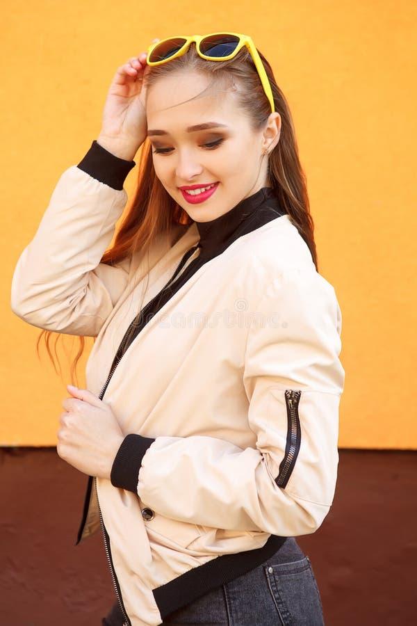 Portret van mooi hipstermeisje in zonnebril op oranje achtergrond Perfecte de zomersamenstelling en stijl stock afbeelding
