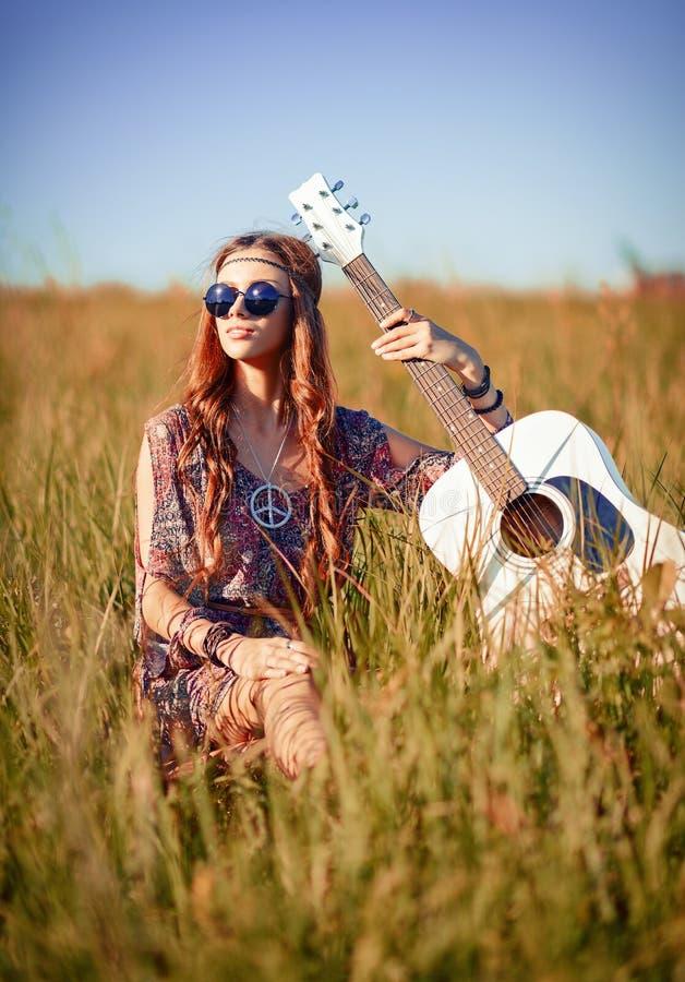 Portret van mooi jong hippiemeisje met gitaar Geschoten op het gebied stock foto