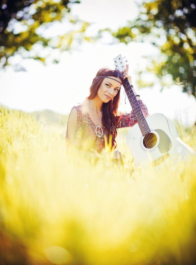 Portret van mooi jong hippiemeisje met gitaar Mistig dalingseiland stock afbeeldingen