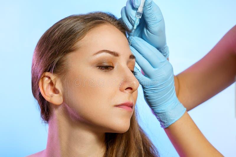 Portret van mooi jong meisje in schoonheidsparlor Cosmetologie-injecties stock afbeeldingen
