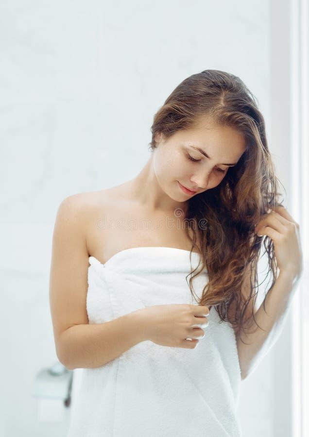 Portret van Mooi Jong Vrouwelijk Model in Bad die Haarolie toepassen Close-up van Sexy Vrouw in Handdoek royalty-vrije stock fotografie