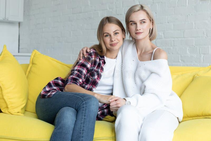 Portret van mooi lesbisch paar in vrijetijdskleding die koesteren, die op gele bank thuis zitten stock afbeeldingen