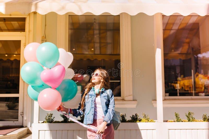 Portret van mooi meisje die denimjasje en het dromerige kijken dragen omhoog wachtend op vrienden om op feestelijke gebeurtenis t royalty-vrije stock foto's