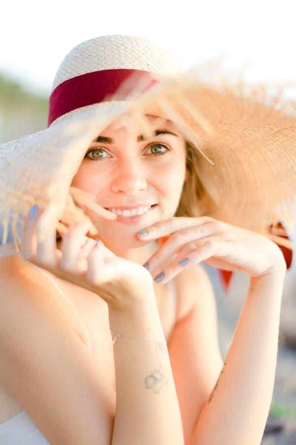 Portret van mooi meisje die hoedenzitting op zandstrand dragen royalty-vrije stock afbeeldingen