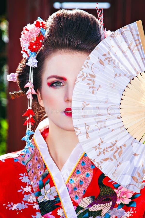 Portret van mooi meisje met buitensporige geishamake-up stock afbeeldingen