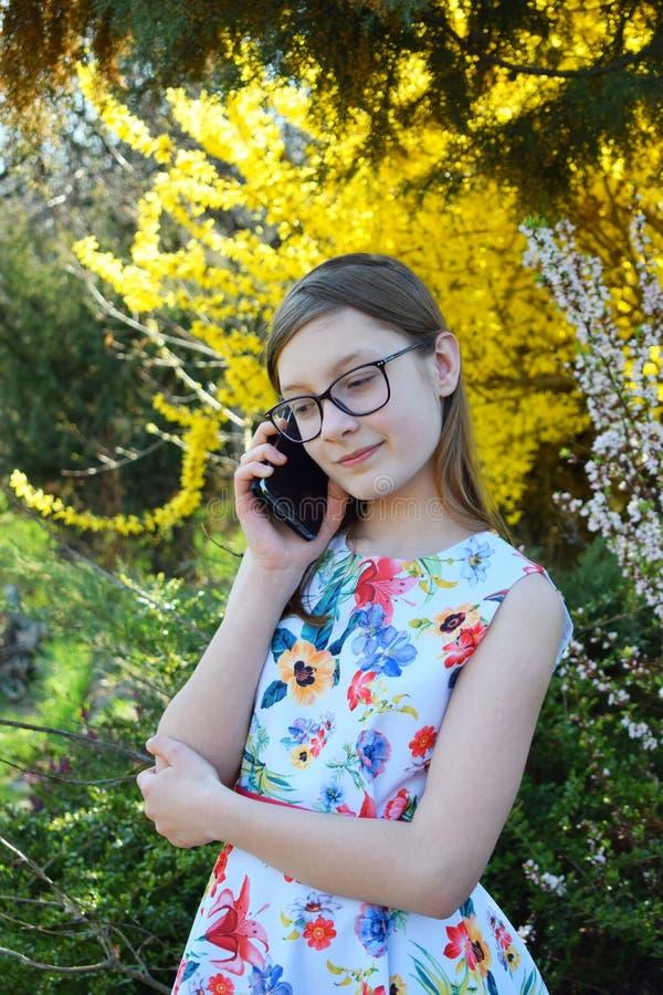 Portret van mooi meisje met glazen en bruine haarbespreking op smartphone Jongelui die teneeger in het groene de lentepark rusten royalty-vrije stock afbeeldingen