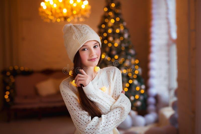 Portret van mooi meisje met lang haar die warme de winterkleren in Kerstmisbinnenland dragen stock afbeeldingen