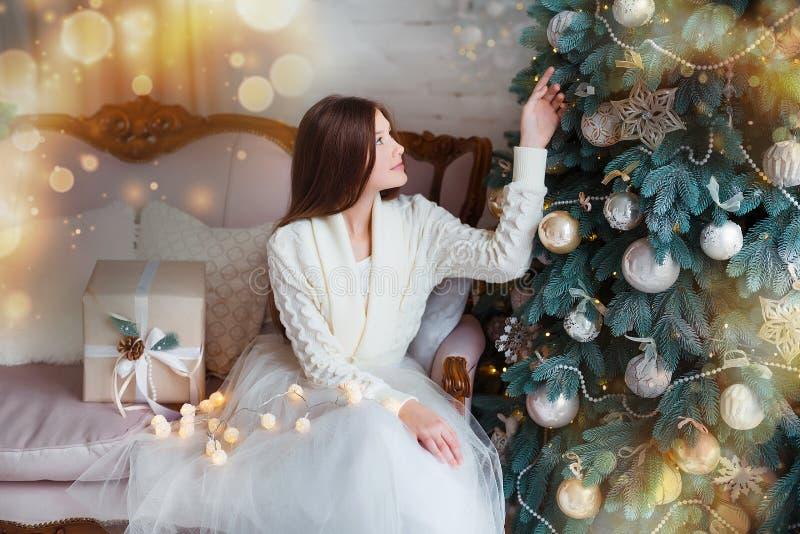 Portret van mooi meisje met lang haar die warme de winterkleren in Kerstmisbinnenland dragen royalty-vrije stock fotografie