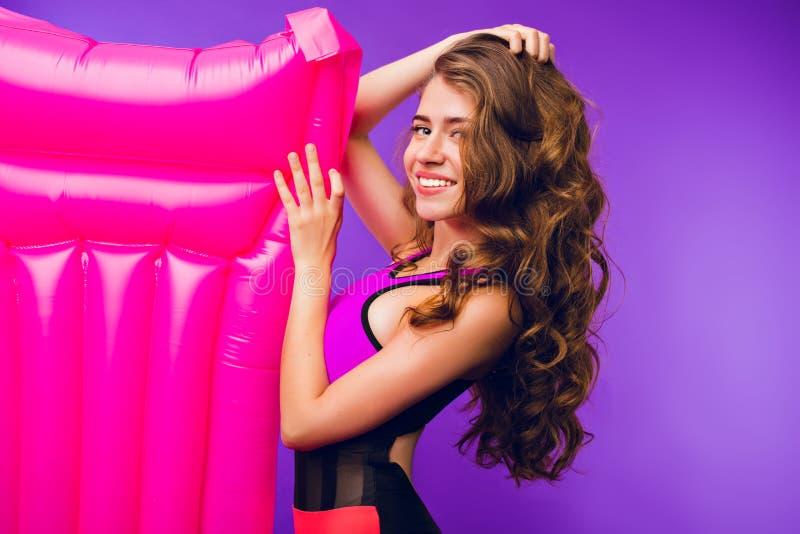 Portret van mooi meisje met lang krullend haar die aan camera op purpere achtergrond in studio glimlachen Zij draagt zwempak en stock afbeelding