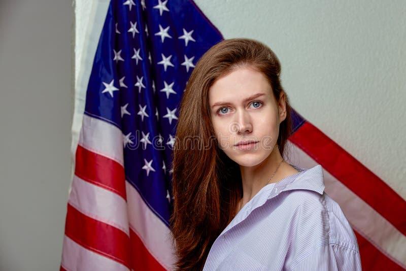 Portret van mooi meisje in overhemd op Amerikaanse vlag dichte omhooggaand als achtergrond royalty-vrije stock afbeelding
