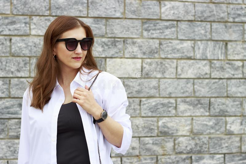 Portret van mooi meisje in zonnebril op grijze concrete achtergrond stock fotografie