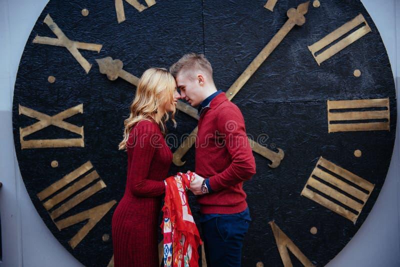 Portret van mooi modieus paar die zich dichtbij de klok bevinden A royalty-vrije stock fotografie