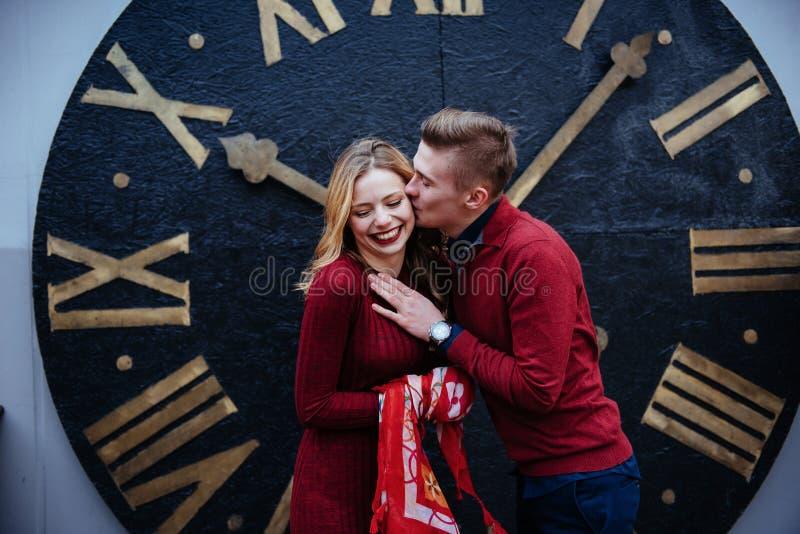 Portret van mooi modieus paar die zich dichtbij de klok bevinden A stock afbeeldingen