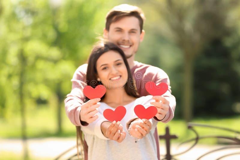 Portret van mooi paar met document harten in openlucht stock fotografie