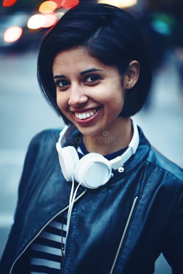 Portret van mooi Spaans latino shor zwart haar van de meisjesvrouw in leerjasje met hoofdtelefoons buiten in de stad van de avond stock afbeeldingen