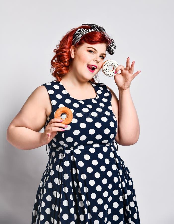 Portret van mooi vrolijk die vet plus groottevrouw speld-op het dragen van een stipkleding over lichte achtergrond wordt ge?solee stock foto