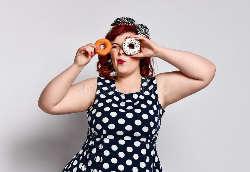 Portret van mooi vrolijk die vet plus groottevrouw speld-op het dragen van een stipkleding over lichte achtergrond wordt ge?solee stock afbeeldingen