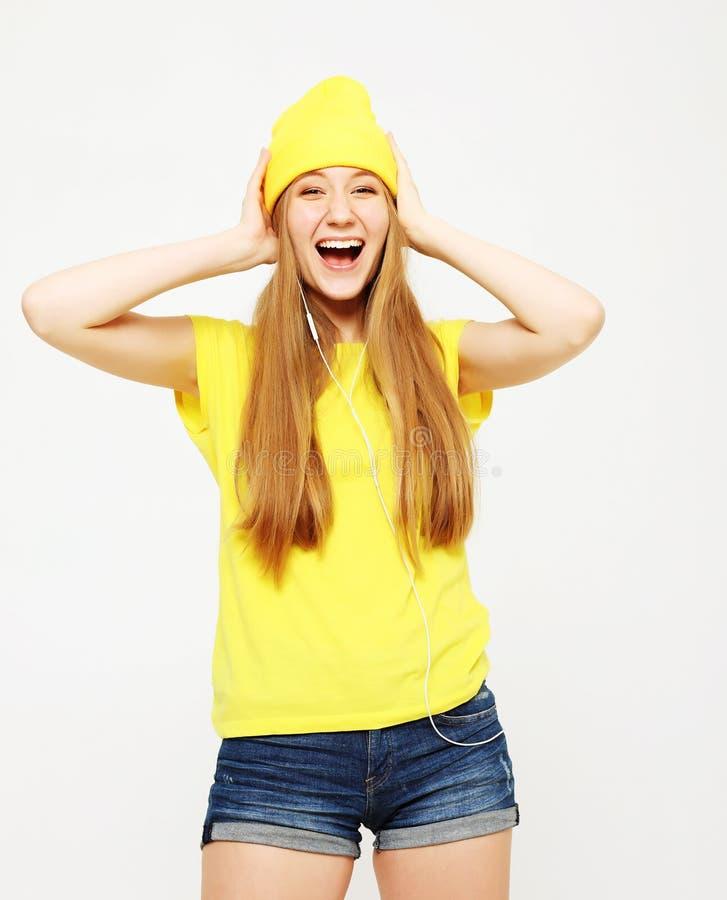 Portret van mooi vrolijk meisje met hoofdtelefoons met het lange haar het glimlachen het lachen bekijken camera stock foto