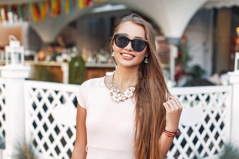 Portret van mooi vrolijk meisje in zonnebril dichtbij wit royalty-vrije stock afbeeldingen