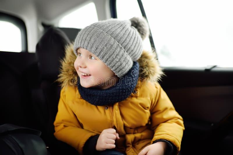 Portret van mooi weinig jongenszitting in autozetel tijdens roadtrip of reis royalty-vrije stock foto