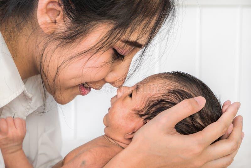 Portret van mooie Aziatische moeder die haar jongen van de zuigelingsbaby op handen en kus met neus houden stock afbeeldingen