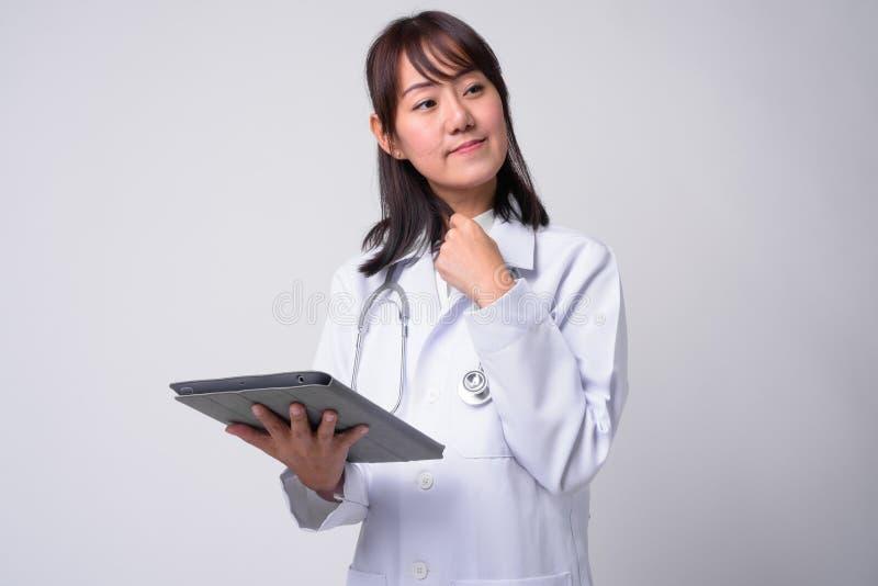 Portret van mooie Aziatische vrouw arts tegen witte achtergrond stock foto