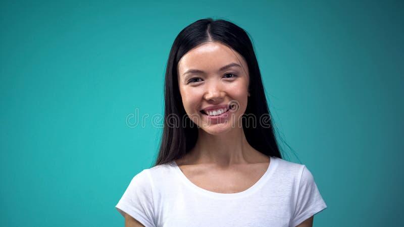 Portret van mooie Aziatische vrouw die camera bekijken die, op blauwe achtergrond wordt geïsoleerd stock afbeeldingen