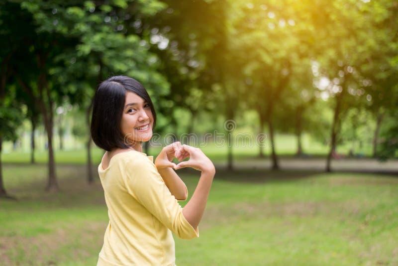 Portret van mooie Aziatische vrouw die de vorm van het handenhart tonen bij openlucht, Gelukkig en, het Positieve denken glimlach stock foto's