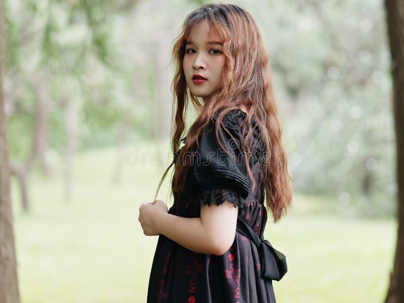 Portret van mooie Aziatische vrouw status in de zomer bos, Chinees meisje die in uitstekende zwarte kleding camera bekijken royalty-vrije stock fotografie