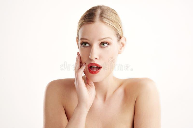 Portret van mooie benieuwd geweeste jonge vrouw met verrast gezicht die zich bij geïsoleerde witte achtergrond bevinden stock fotografie