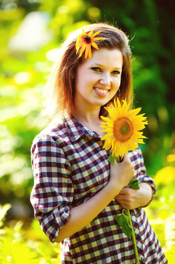 Portret van mooie blije vrouw met zonnebloem stock foto
