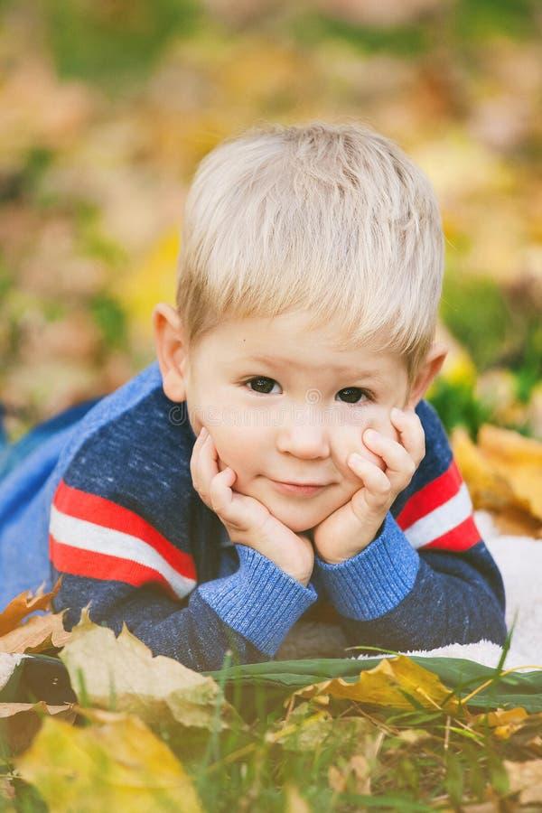 Portret van mooie blonde nakomelingen die op ou van de herfstbladeren leggen stock afbeeldingen