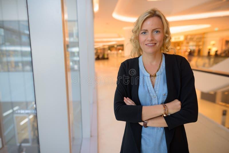 Portret van mooie blondeonderneemster binnen winkelcomplex stock foto