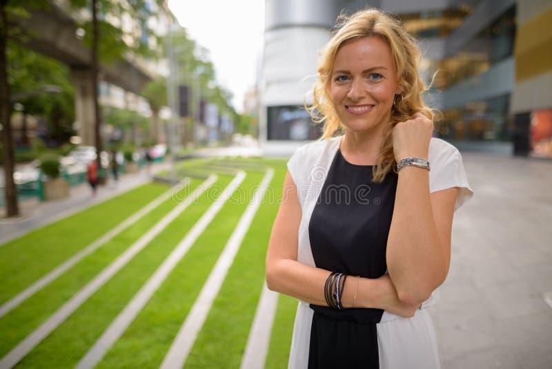 Portret van mooie blondeonderneemster die in openlucht glimlachen stock afbeelding
