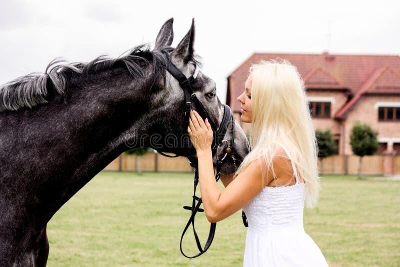 Portret van mooie blondevrouw en grijs paard bij het huwelijk royalty-vrije stock afbeelding