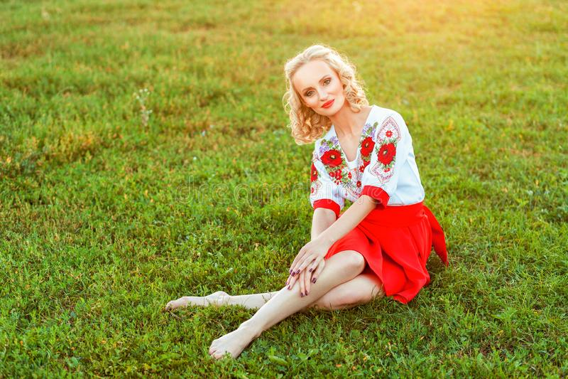 Portret van mooie blondevrouw met make-up en krullend kapsel in het modieuze kleding stellen met geluk op groen gras en het kijke royalty-vrije stock foto's