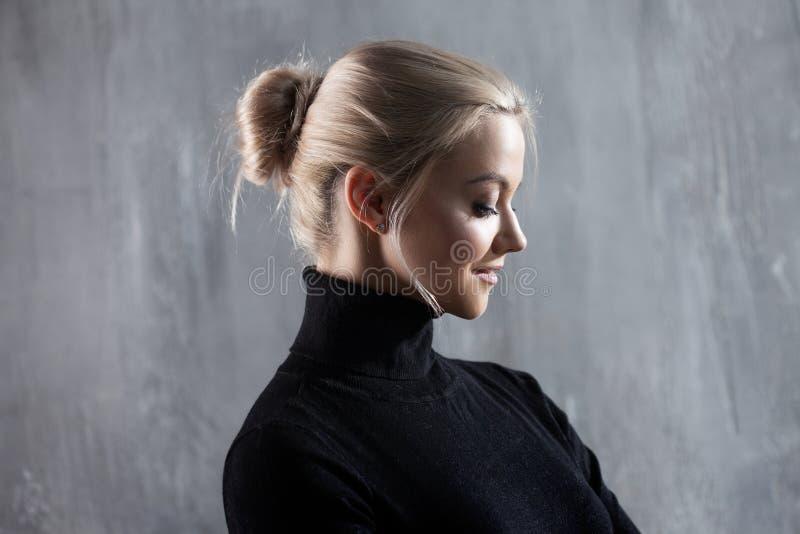 Portret van mooie blondevrouw Rust en zelfvertrouwen Mooi volwassen meisje in zwarte col, grijze achtergrond stock foto
