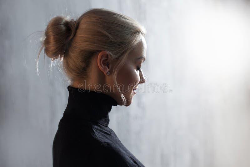 Portret van mooie blondevrouw Rust en zelfvertrouwen Mooi volwassen meisje in zwarte col, grijze achtergrond royalty-vrije stock foto