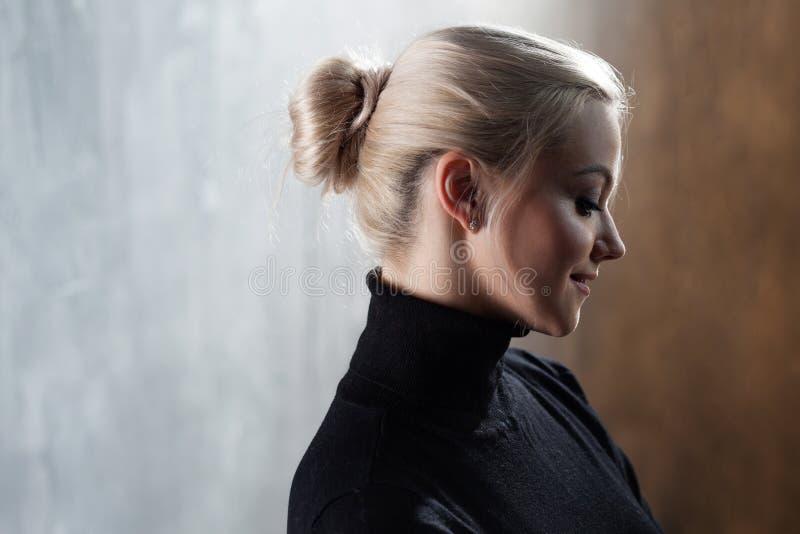 Portret van mooie blondevrouw Rust en zelfvertrouwen Mooi volwassen meisje in zwarte col, grijze achtergrond stock afbeeldingen