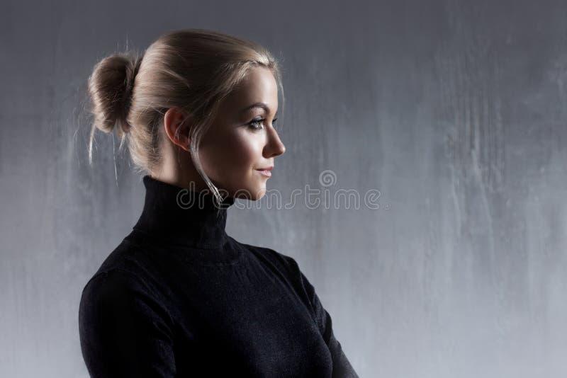 Portret van mooie blondevrouw Rust en zelfvertrouwen Mooi volwassen meisje in zwarte col, grijze achtergrond stock afbeelding