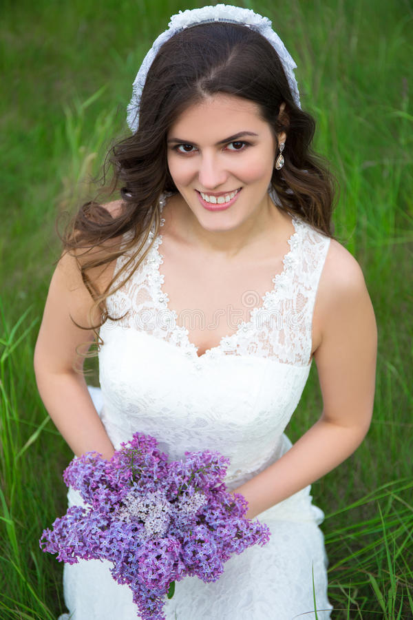 Portret van mooie bruid met boeket van lilac bloemen stock afbeeldingen
