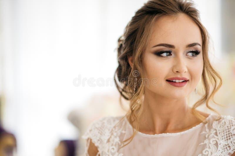 Portret van mooie bruid in witte huwelijkskleding die zich in boudoir ruimte en het glimlachen bevinden royalty-vrije stock foto's