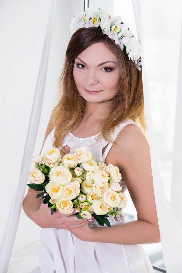Portret van mooie bruid in witte kleding met bloemen dichtbij royalty-vrije stock foto's