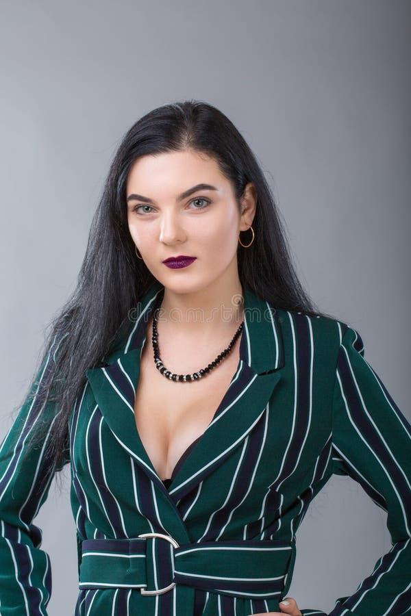 Portret van Mooie die onderneemsterstudio op grijze achtergrond wordt geschoten Charmante en zekere ernstige donkerbruine vrouw i royalty-vrije stock afbeelding
