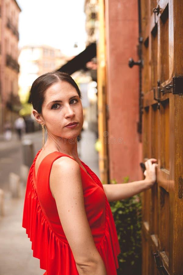 Portret van mooie donkerbruine jonge vrouw die rode kleding wat betreft oude houten deur in de straat dragen De foto van de manie stock afbeelding